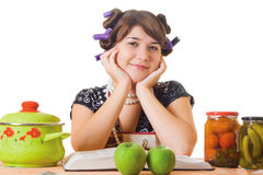 Housewife sitting at the table. Smiling housewife sitting at the table with food Royalty Free Stock Photos