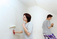 Housewife with son painting wall to white Stock Photos