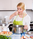 Housewife and spoiled food. Young woman pinched her nose avoiding bad smell from pan stock photography