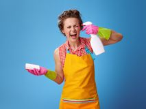 Housewife with sponge wanting to shoot herself from a bottle. Big cleaning time. stressed young housewife in a yellow apron with kitchen sponge wanting to shoot royalty free stock photography
