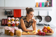 Housewife standing near jars with fruits jam Royalty Free Stock Photos