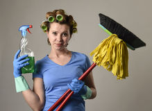 Housewife stereotype hair rollers and washing gloves holding mop broom and detergent spray bottle Stock Photos