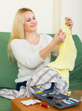 Housewife stitching tears of clothes Stock Images