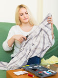 Housewife stitching tears of clothes Stock Photo