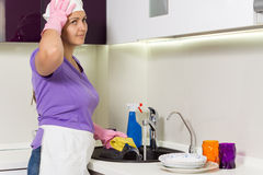 Housewife straightening her cap as she works Stock Photography