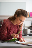 Housewife studying fresh spices herbs in kitchen stock image