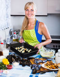 Housewife stuffing mollusc shells Stock Photos