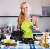 Housewife stuffing mollusc shells Stock Photography
