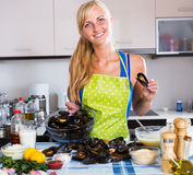Housewife stuffing mollusc shells Royalty Free Stock Images
