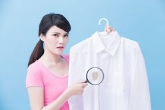 Housewife take clean shirt. House take clean shirt and magnifying on the blue background stock image