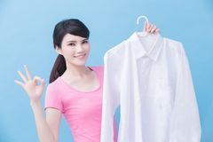 Housewife take clean shirt. House take clean shirt and show ok to you on the blue background royalty free stock photo