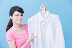 Housewife take clean shirt. House take clean shirt and show to you on the blue background stock photography