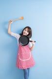 Housewife take wok and spoon Stock Photo