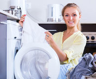 Housewife taking clothes out machine Stock Photography