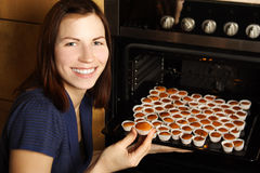 Housewife taking cupcakes from oven Stock Images