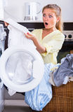Housewife taking dirty clothes out washing machine Stock Photos