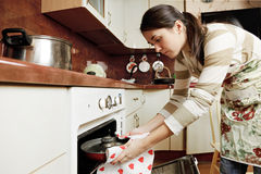 Housewife taking frying pan from oven Stock Photos