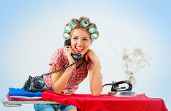 Housewife talking on the phone while ironing Royalty Free Stock Images