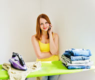 Housewife talking on the phone while ironing Stock Image