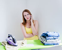 Housewife talking on phone while ironing on grey background Royalty Free Stock Photos