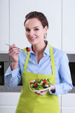 Housewife tasting salad in the kitchen Royalty Free Stock Image