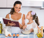 Housewife teaching daughter to prepare omelette and smiling Stock Image