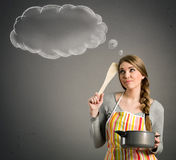 Housewife thinking what to cook. Young beautiful housewife with empty think clouds, concept - What to cook today Stock Photography