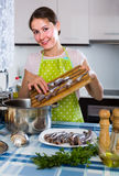 Housewife trying new recipe of sprattus in kitchen Stock Photography