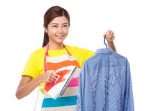 Housewife use iron for straighten of the shirt Stock Images