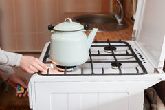 Housewife use matches to ignite a fire in kitchen gas stove. Stock Photo