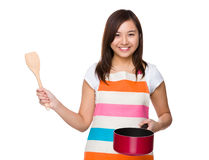 Housewife use of the saucepan and wooden ladle Royalty Free Stock Photo