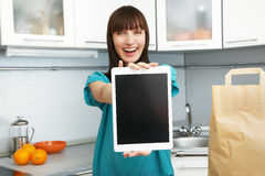 Housewife uses a tablet computer in the kitchen Stock Photos