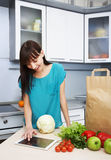 Housewife uses a tablet computer in the kitchen Stock Images