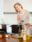Housewife using laptop while cooking soup Stock Photos