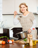 Housewife using laptop while cooking soup with vegetable Stock Photography