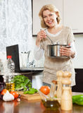 Housewife using notebook while cooking soup Stock Image