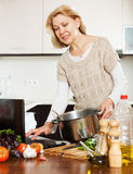 Housewife using notebook while cooking Royalty Free Stock Photography