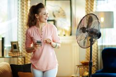 Housewife using smart home app in smartphone to control fan