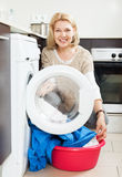 Housewife using washing machine at home Royalty Free Stock Image