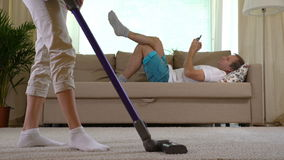 Housewife vacuuming carpet and her husband lying on the sofa with smartphone stock footage