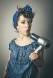 Housewife in vintage clothes with hair dryer. Half body portrait of housewife in vintage clothes pointing modern hair dryer at face Stock Photo