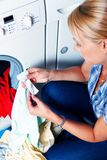 Housewife washing. A young housewife with washing machine and clothes. Washing day royalty free stock image