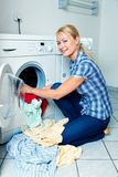 Housewife washing. A young housewife with washing machine and clothes. Washing day royalty free stock photography