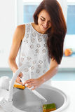Housewife is washing dishes in the kitchen. Attractive smiling housewife is washing dishes in the kitchen. She is scrubbing a dish with a sponge royalty free stock photos