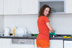 Housewife washing dishes in rubber gloves Stock Images