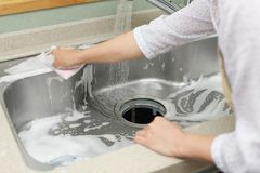 Woman washing the kitchen sink. Housewife washing the kitchen sink stock photo
