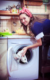 Housewife with washing machine and towels. Stock Photo
