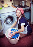 Housewife with washing machine and towels. Stock Photos