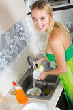 Housewife washing plates with sponge Stock Photos