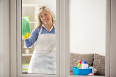 Housewife washing windows Royalty Free Stock Photos